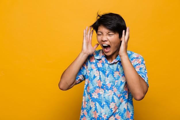 Кричащий эмоциональный молодой азиатский человек позирует изолированным над желтым пространством.