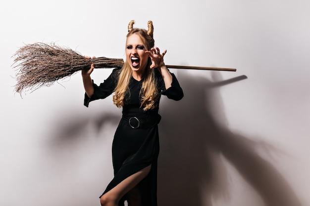 흰 벽에 서있는 악한 마법사 비명. 빗자루를 들고 검은 드레스에 뱀파이어 소녀입니다.