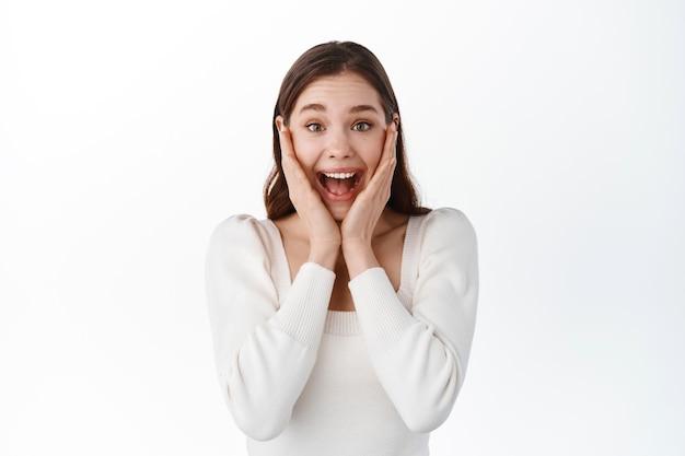 悲鳴を上げる少女は驚きと驚きに見え、勝利と喜びを感じ、顔に手をつないで笑い、素晴らしい素晴らしいニュースを信じないで見つめ、勝利を祝い、白い壁の上に立っています