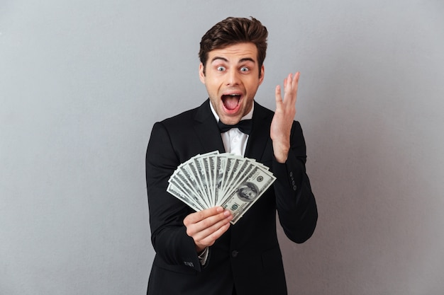 Screaming happy man in official suit holding money.