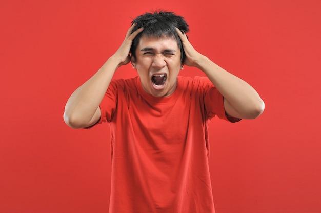 비명, 증오, 분노. 울고 있는 감정적인 화난 아시아 남자는 비명을 지르며 붉은 배경에 고립되어 있습니다. 감정적, 인간의 감정, 표정.
