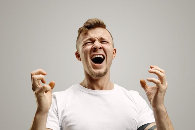 叫び、憎しみ、怒り。灰色のスタジオの背景で叫んで泣いている感情的な怒っている男。感情的な、若い顔。男性の半分の長さの肖像画。人間の感情、顔の表情の概念。