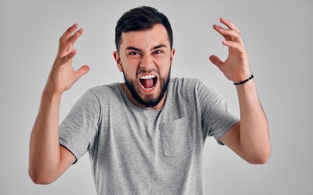 Крики, ненависть, ярость. плачет эмоциональный сердитый человек кричит на сером фоне студии. эмоциональное молодое лицо. мужской поясной портрет. человеческие эмоции, концепция выражения лица.