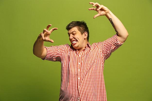 叫び、憎しみ、怒り。緑のスタジオの背景で叫んで泣いている感情的な怒っている男。感情的な、若い顔。男性の半身像。人間の感情、表情の概念。トレンディな色