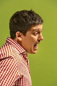 叫び、憎しみ、怒り。緑のスタジオの背景で叫んで泣いている感情的な怒っている男。感情的な、若い顔。男性の半身像。プロフィール