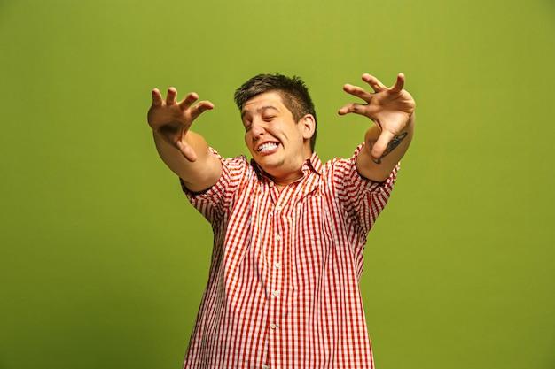 Крики, ненависть, ярость. плачет эмоциональный сердитый человек кричит на фоне зеленой студии. эмоциональное молодое лицо. мужской поясной портрет.