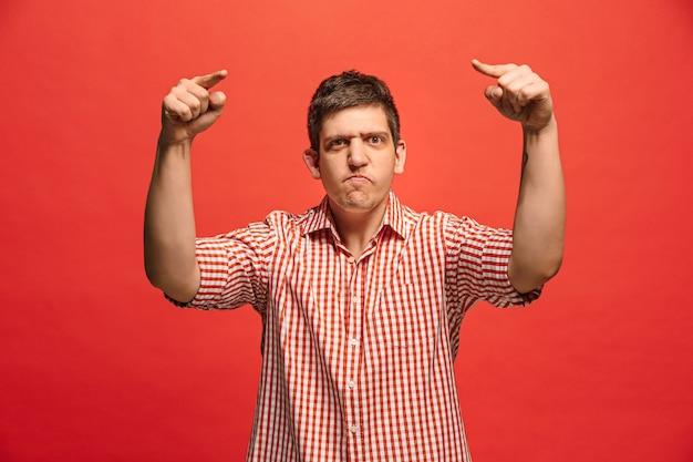 叫び、憎しみ、怒り。赤いスタジオの背景で叫んで泣いている感情的な怒っている男。感情的な、若い顔。男性の半身像。人間の感情、表情の概念。トレンディな色