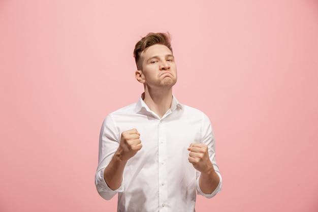 Urla, odio, rabbia. uomo arrabbiato emozionale gridante che grida sullo studio rosa
