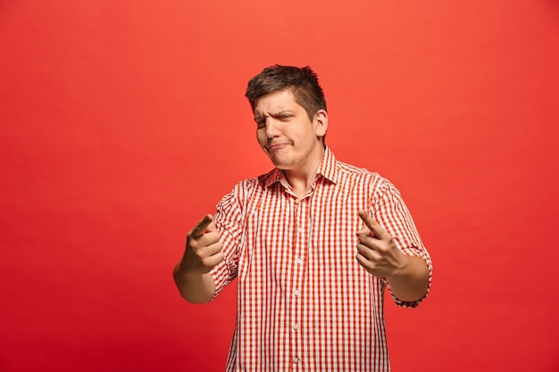 Screaming, hate, rage. crying emotional angry man screaming on red studio background. emotional, young face. male half-length portrait.