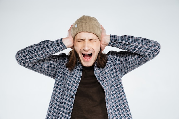 Screaming hipster covering ears
