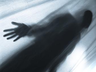 Screaming human pressing through fabric curtain as horror background