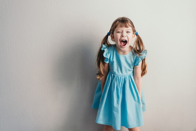 Screaming little girl in blue dress on neutral wall