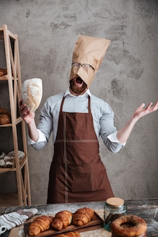 Screaming man baker standing with paper bag on head
