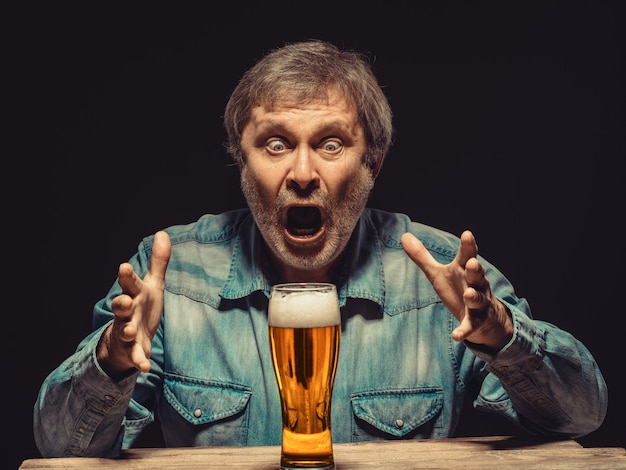 Screaming man in denim shirt with glass of beer