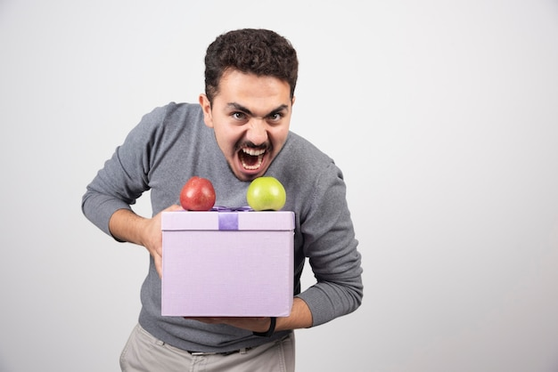 Кричащий мужчина держит фиолетовую коробку с яблоками.