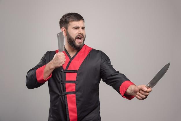 Uomo di grido che tiene due coltelli sul muro grigio