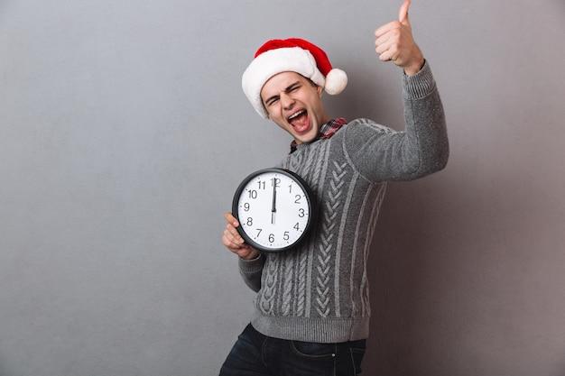 Кричащий мужчина в свитере и рождественской шляпе держит часы и показывает палец вверх, глядя
