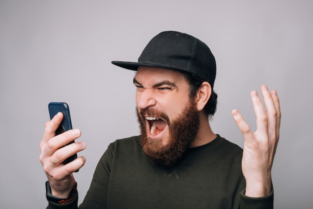 Screaming man is looking to his phone on white background.