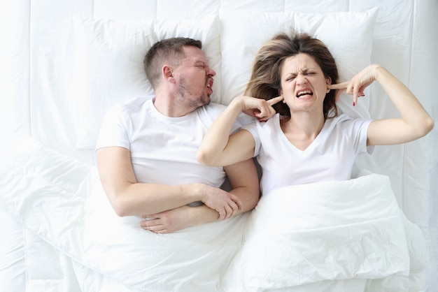 Screaming man lies in bed with depressed woman family problems and misunderstanding of each