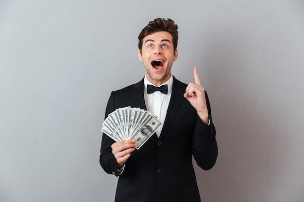 Screaming man in official suit holding money pointing.