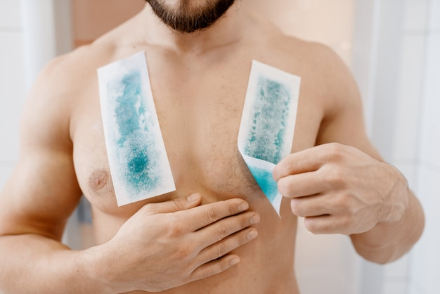 Screaming man removes chest hair, morning hygiene, waxing depilation. male person resting in bathroom, skin and body treatment procedures