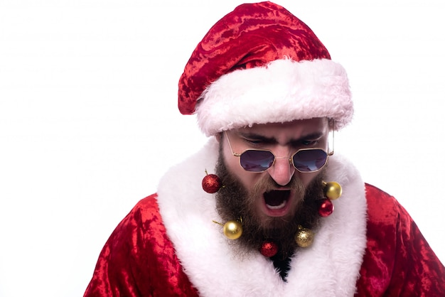 Screaming man in santa claus costume, black glasses and christmas toys in the beard copy-space
