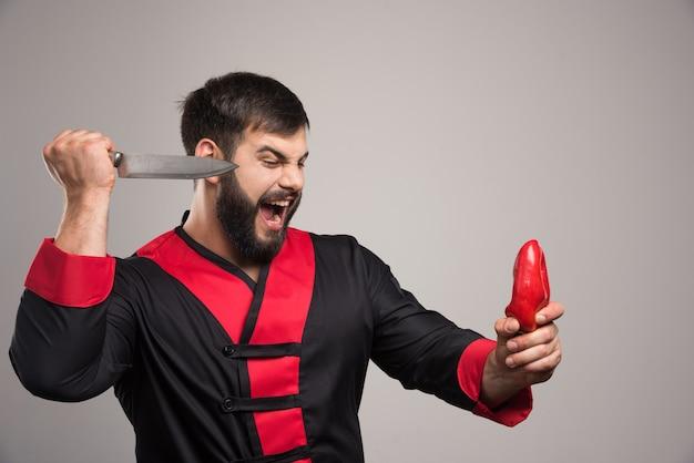 Uomo di grido che prova a tagliare un peperone rosso.