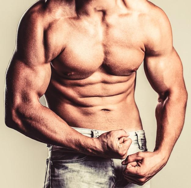 よく訓練された体、上腕二頭筋、腹筋、胸筋を持った悲鳴を上げる男。筋肉質の男性は筋肉を緊張させ、悲鳴を上げます。白い背景の上にポーズをとる筋肉のボディービルダー