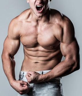 よく訓練された体、上腕二頭筋、腹筋、腹筋と身に着けている男を叫んでいます。筋肉質の男性は筋肉を緊張させ、悲鳴を上げます。白い背景の上にポーズをとる筋肉のボディービルダー。