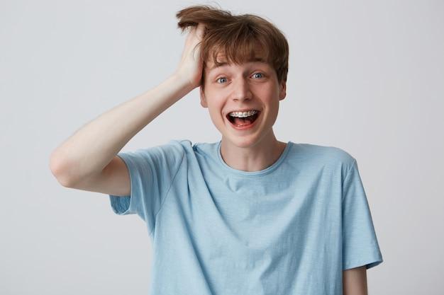 片手で頭を抱えた若い男が幸せと興奮の叫び