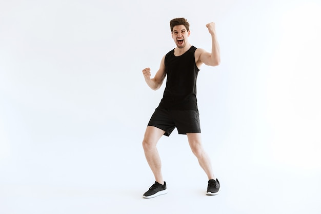 Screaming positive young sports man running and make winner gesture.
