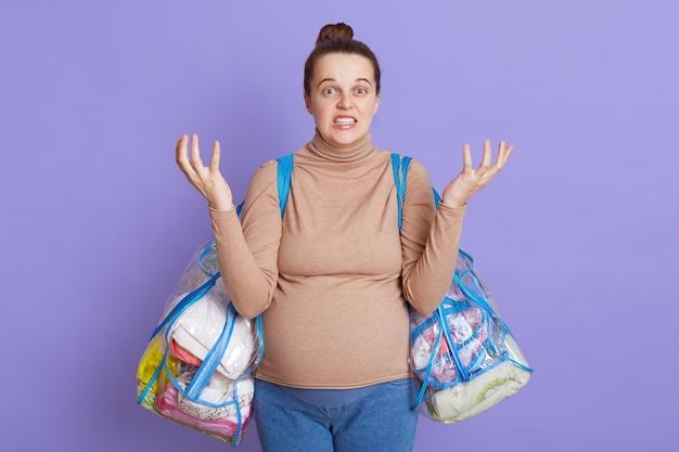 Кричащая беременная женщина позирует над сиреневой стеной, кричит и поднимает руки