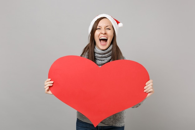 Screaming santa girl in gray sweater scarf christmas hat holding empty blank red heart isolated on grey background in studio. happy new year 2019 celebration holiday party concept. mock up copy space.