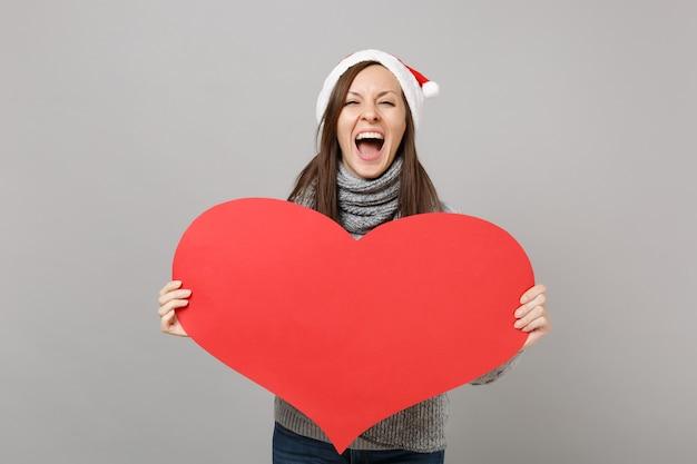 スタジオで灰色の背景に分離された空の空白の赤いハートを保持している灰色のセータースカーフクリスマス帽子でサンタの女の子を叫んでいます。明けましておめでとうございます2019お祝いホリデーパーティーのコンセプト。コピースペースをモックアップします。