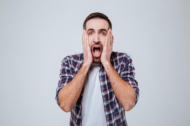 Кричащий шокированный бородатый мужчина в рубашке
