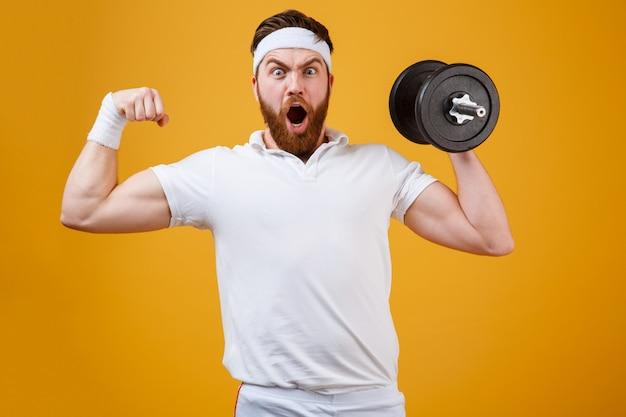 Кричащий спортсмен держа гантель и показывая бицепс