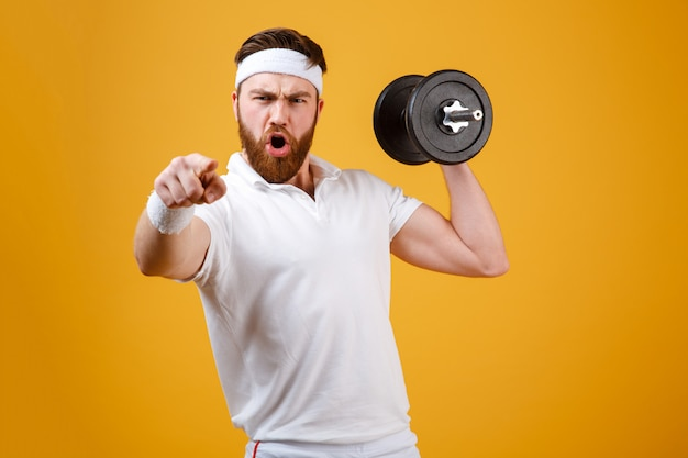 Screaming sportsman holding dumbbell