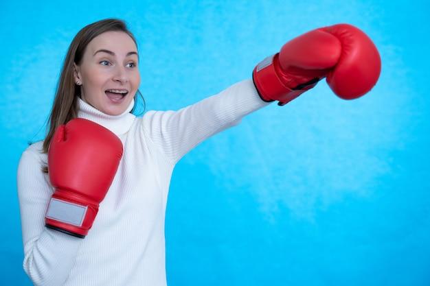 ボクシンググローブを身に着けている青い壁の壁の上に孤立したポーズをとって叫んで強い若い女性ボクサー。