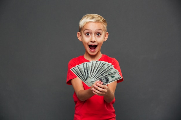 Screaming surprised little boy child showing money.