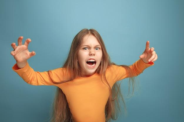 Urlando ragazza adolescente sorpresa su uno sfondo blu studio. le espressioni facciali e le emozioni delle persone concetto.