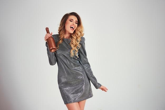 Кричащая женщина держит бутылку шампанского