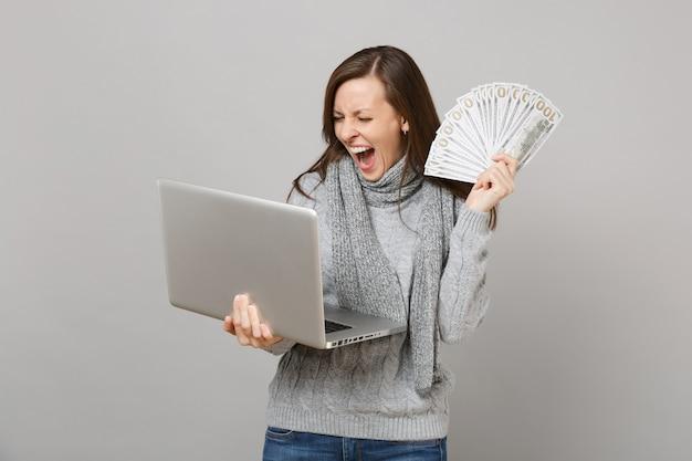 Кричащая женщина в свитере, работающая на портативном компьютере, держит много кучу долларов, банкноты, наличные деньги, изолированные на сером фоне. консультации по лечению здорового образа жизни онлайн в холодное время года.