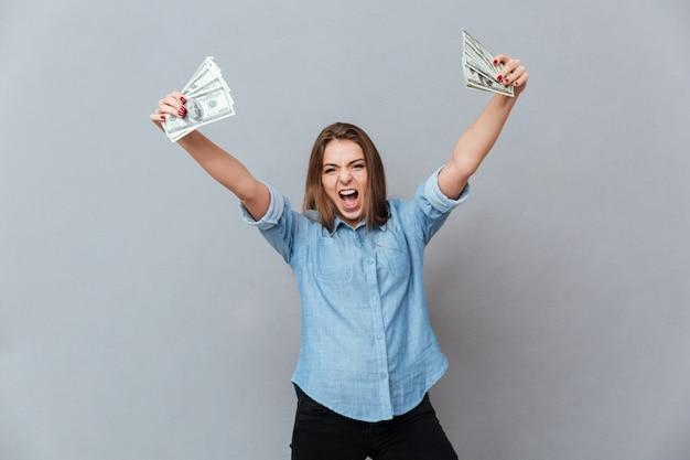 Donna di grido in camicia che tiene i soldi