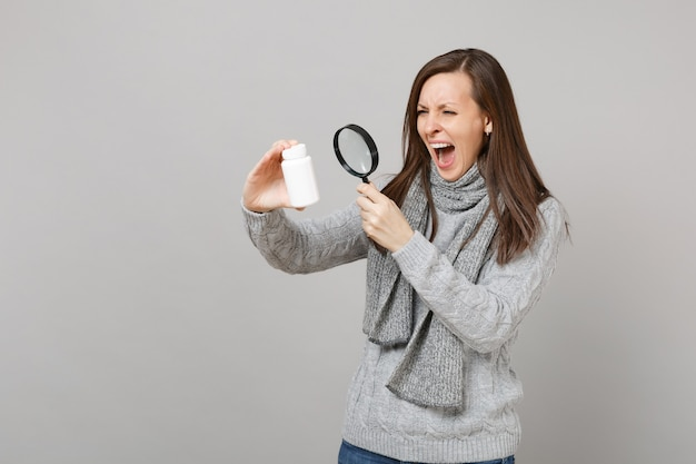 Screaming woman in sweater looking on medication tablets aspirin pills in bottle with magnifying glass isolated on grey background. healthy lifestyle, ill sick disease treatment, cold season concept.