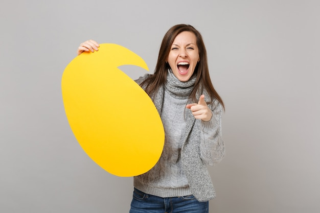 Screaming woman in sweater, scarf point index finger on camera, hold empty blank say cloud, speech bubble isolated on grey background. healthy fashion lifestyle, people emotions, cold season concept.