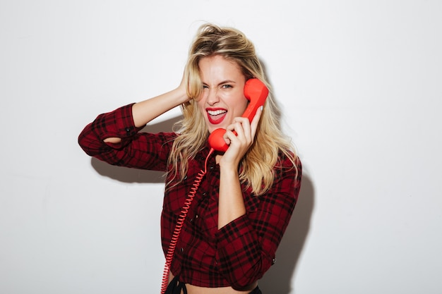 Screaming woman talking by red retro telephone.