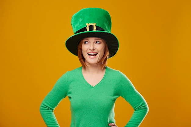 Screaming woman with leprechaun's hat looking at copy space