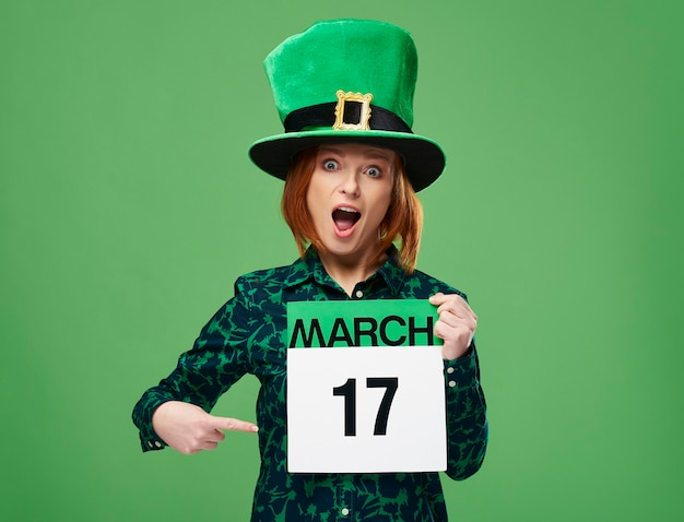 Screaming woman with leprechaun's hat pointing at calendar