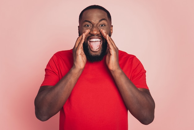 Screaming young african man with hand mouth isolated over pink background.