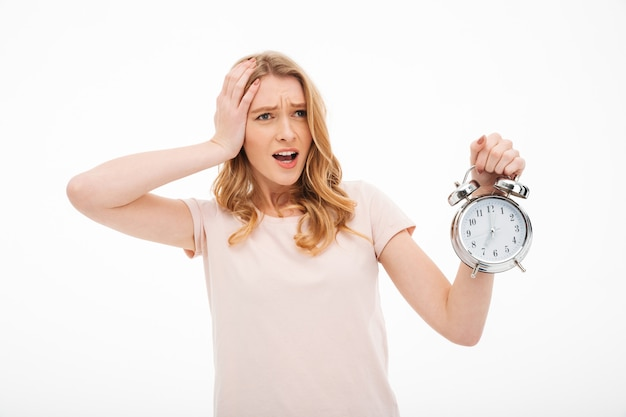 Screaming young confused woman holding alarm clock.